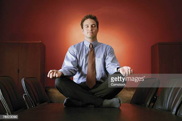 Businessman meditating on conference table