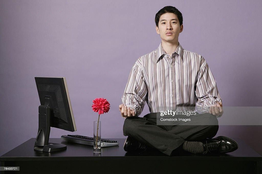 Businessman meditating on top of desk : Stockfoto