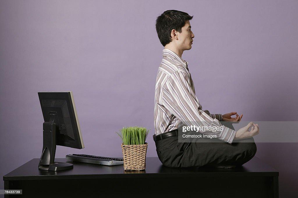 Businessman meditating on top of desk : Stock Photo