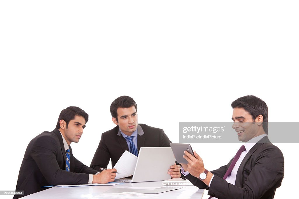 Businessman messaging as colleagues watch on : Stock Photo
