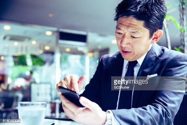 仕事の後の彼のクライアントのメッセージングの実業家 - 金融関係の職業 ストックフォトと画像