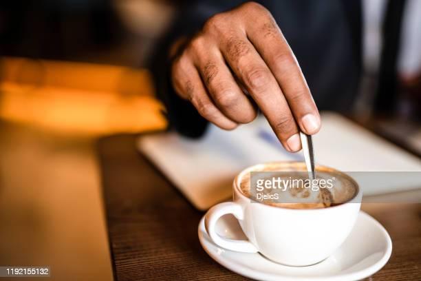 コーヒーの手を混ぜるビジネスマンがクローズアップ。 - 混ぜる ストックフォトと画像