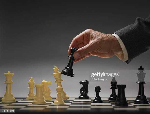 Businessman moving chess piece