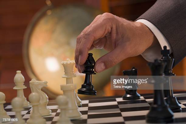 businessman moving chess piece - mondo beat foto e immagini stock