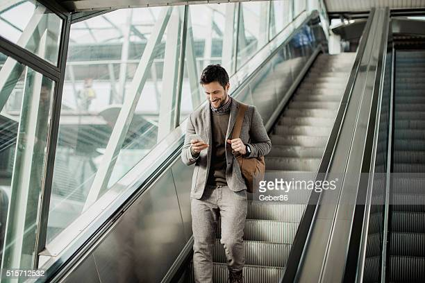 Businessman moving down escalator