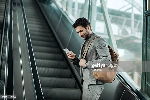 Businessman moving up escalator