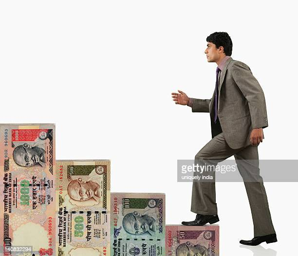 Businessman moving up on a staircase of money