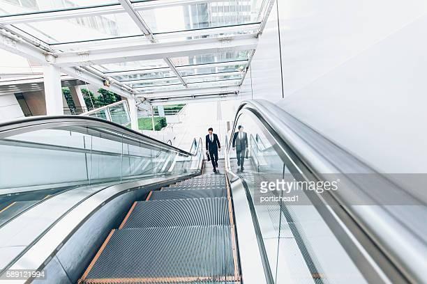 Businessman moving up on escalator