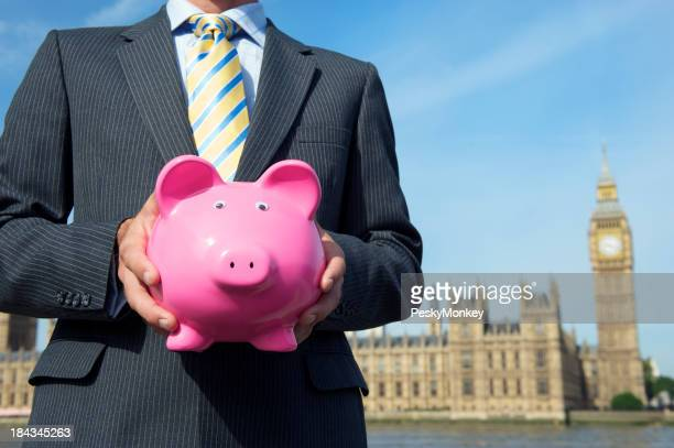 Businessman MP Holding Piggy Bank before Houses of Parliament
