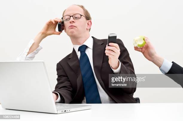 Un homme d'affaires de multitâche au bureau avec téléphone et ordinateur