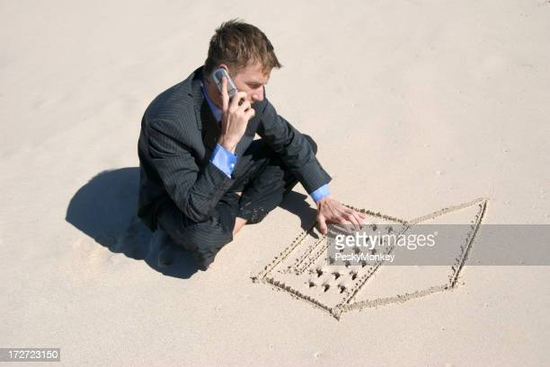 Businessman Multi-Tasking on the Beach Typing and Talking