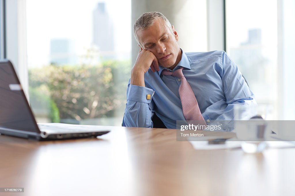 Businessman napping at desk in office : Stock Photo