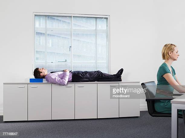 Businessman Napping on Cabinets