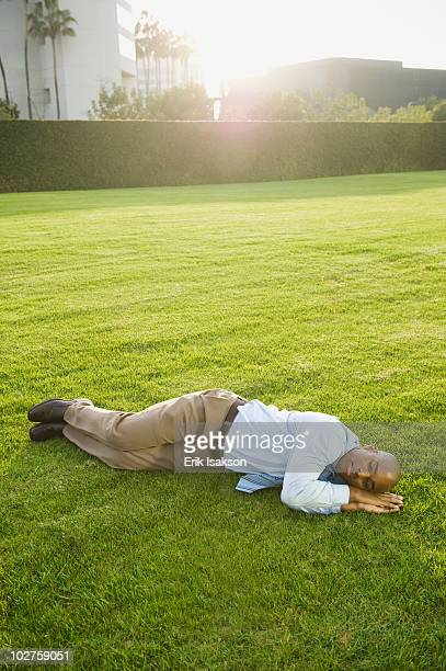 Businessman napping on lawn