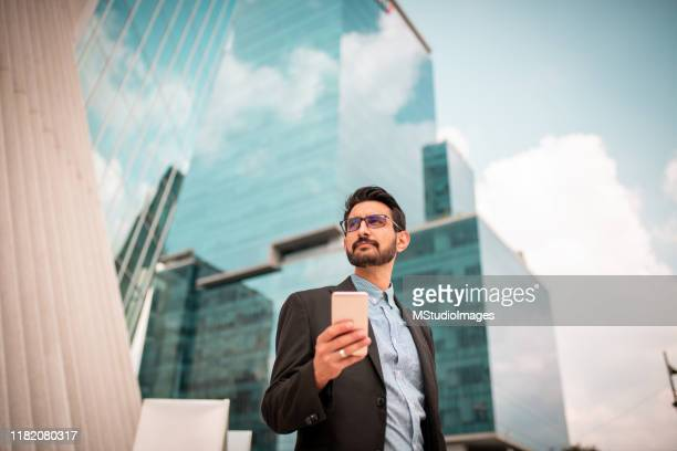 businessman near skyscrapers - directly below stock pictures, royalty-free photos & images