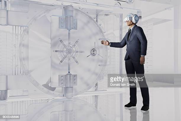 Businessman near vault wearing virtual reality goggles