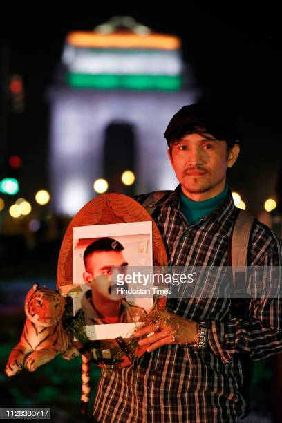 A businessman Neeraj holding a photo of IAF pilot Abhinandan Varthaman to celebrate his release from Pakistan at India Gate on March 1 2019 in New...