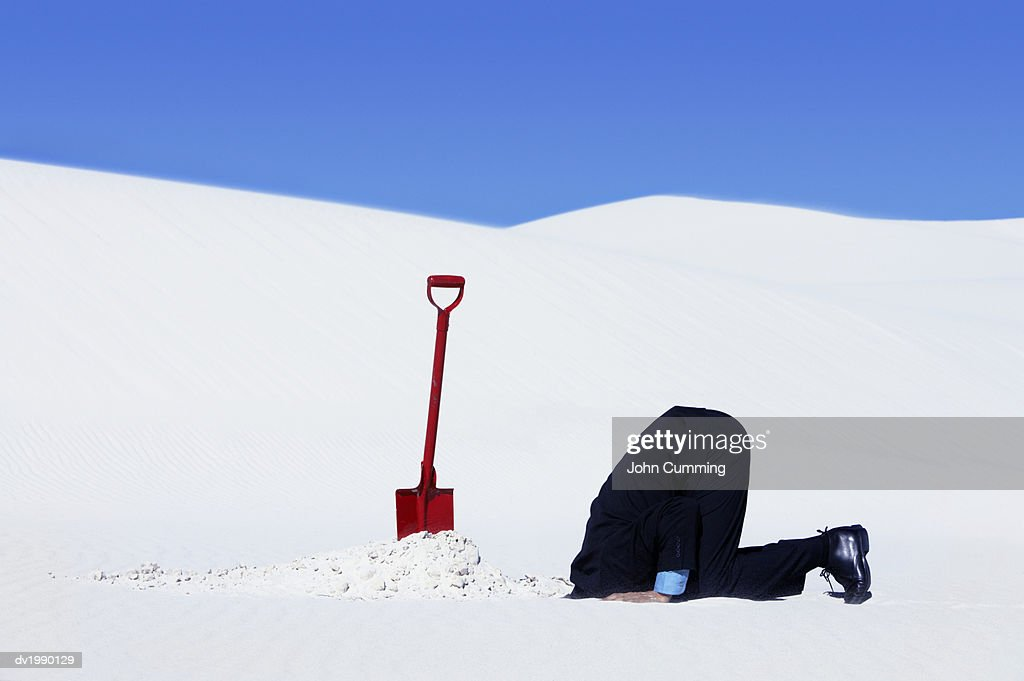 Businessman Next to a Spade Hiding His Head in a Hole in the Snow : Stock Photo