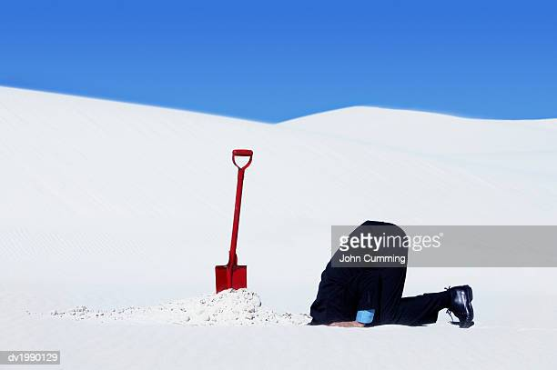 Businessman Next to a Spade Hiding His Head in a Hole in the Snow