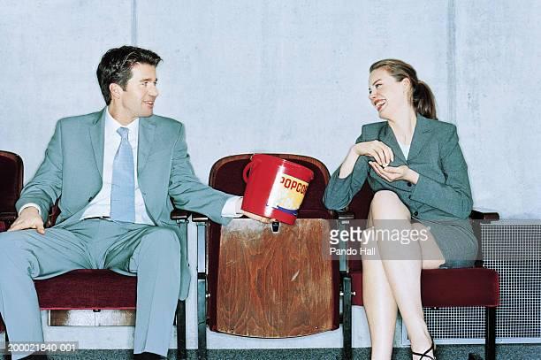 Businessman offering businesswoman popcorn