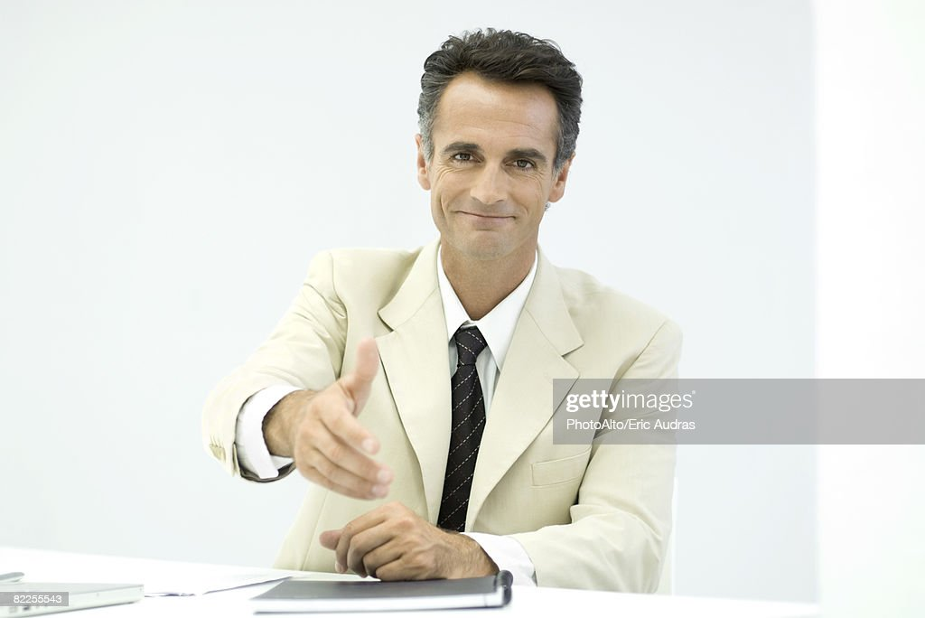 Businessman offering his hand to camera, smiling : Stock Photo