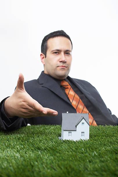 Businessman offers a miniature house