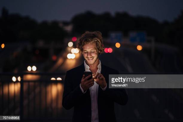 Businessman on a bridge at night using cell phone