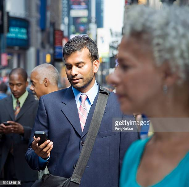 Businessman on a busy street reading a text message