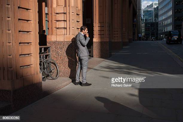 A businessman on a cigarette break smokes outside offices in late summer sunshine on 8th September 2016 in the City of London England UK The young...