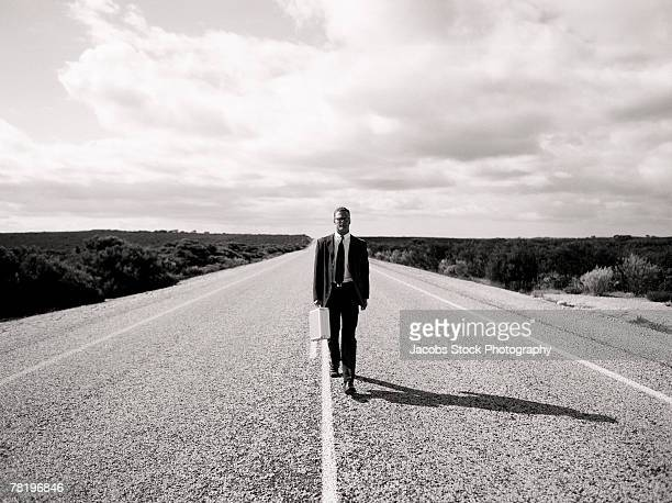 businessman on a desert highway - en medio de la carretera fotografías e imágenes de stock