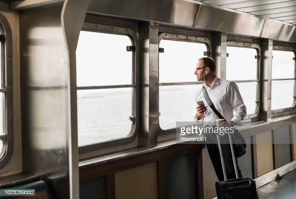 businessman on a ferry looking out of window - ferry stock pictures, royalty-free photos & images
