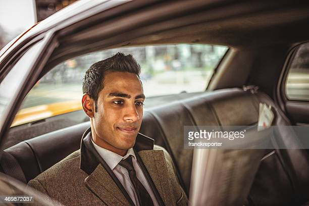 Businessman on a taxi cab reading newspaper