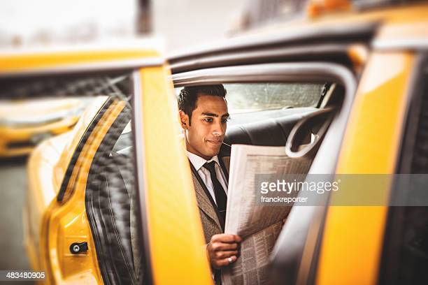 Businessman on a yellow cab reading newspaper