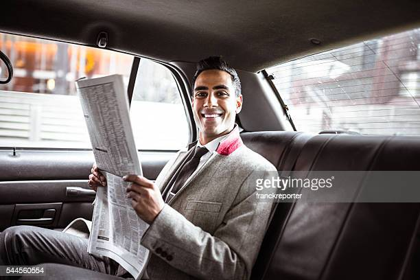 Businessman on a yellow cab reading the newspaper