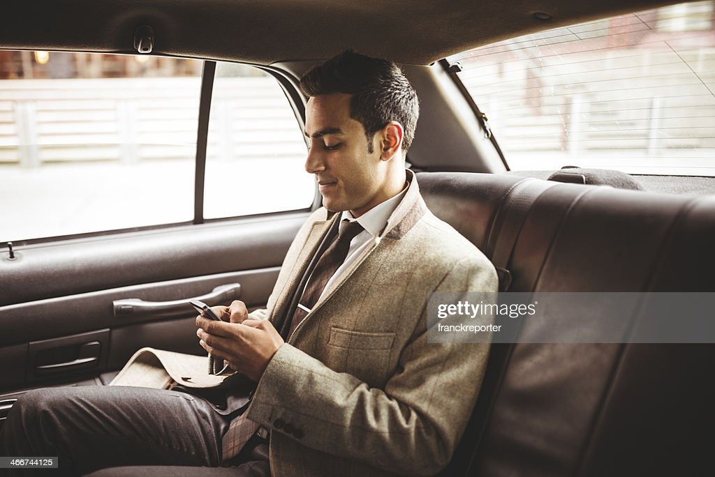 Empresário em um táxi amarelo ainda mensagens de texto : Foto de stock