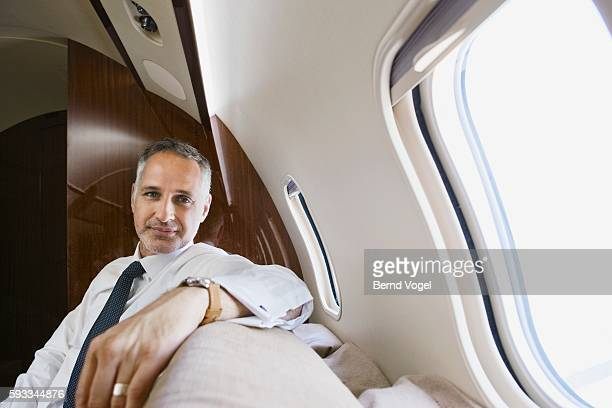 businessman on airplane - prosperity stock pictures, royalty-free photos & images