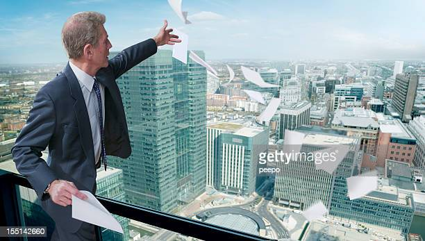 Businessman On Balcony Above City Throwing Away Paper