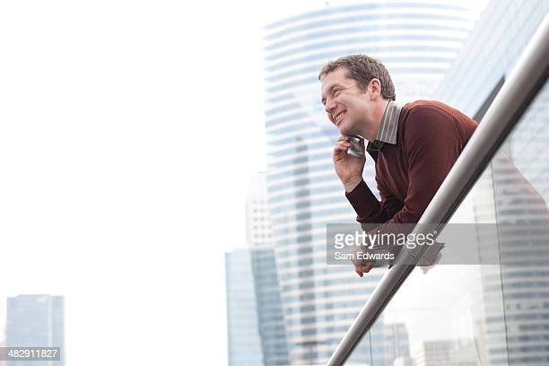 Businessman on balcony using his mobile phone