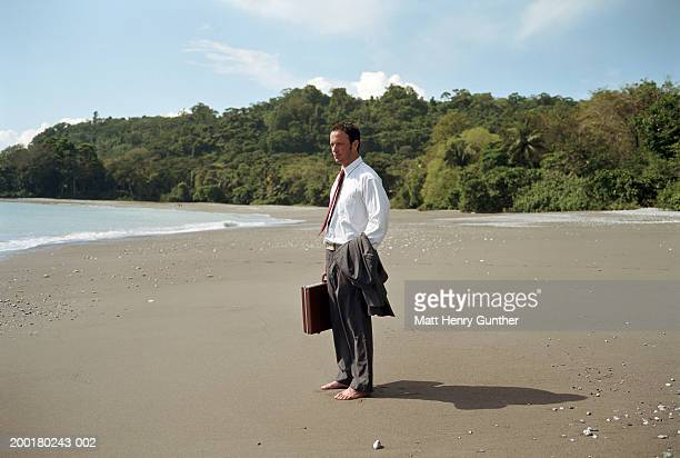 businessman on beach holding surfboard and briefcase, rear view - one man only stock pictures, royalty-free photos & images