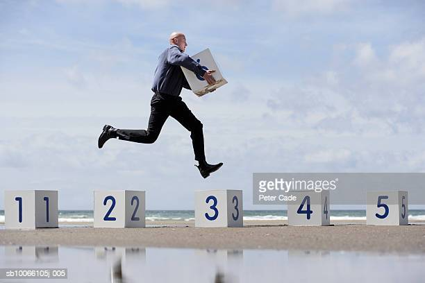 Businessman on beach jumping on white numbered boxes, side view