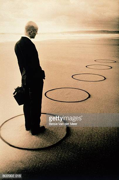 Businessman on beach, standing in circle drawn in sand (toned B&W)