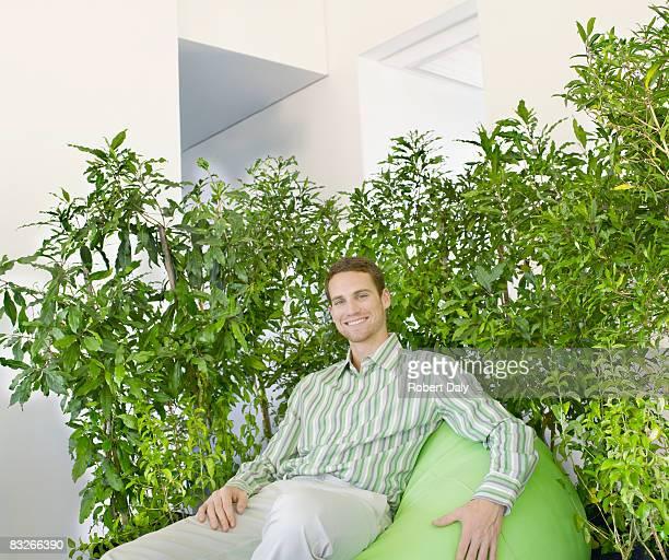 Geschäftsmann auf dem Sitzsack umgeben von Pflanzen
