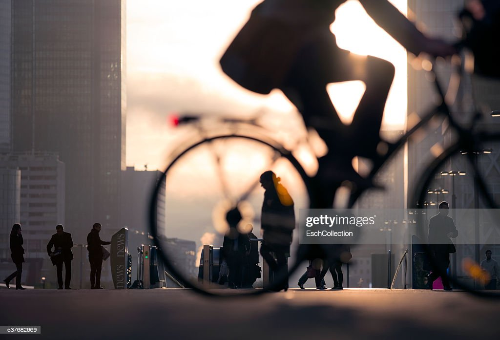 Businessman on bicycle passing skyline La Defense : Stock-Foto