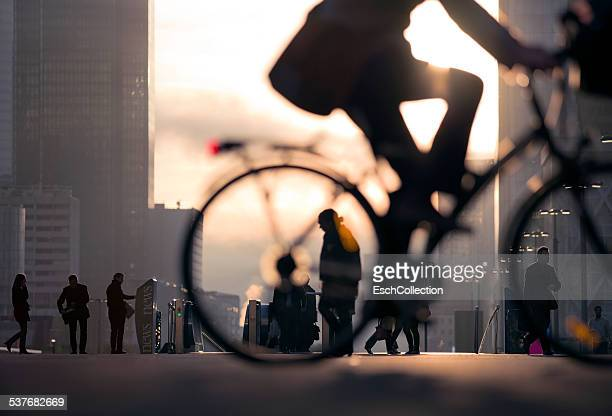 businessman on bicycle passing skyline la defense - city life stock pictures, royalty-free photos & images