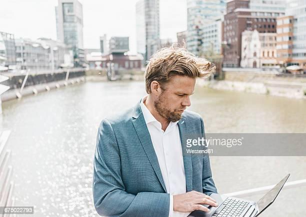 businessman on bridge using laptop - medienhafen stock-fotos und bilder