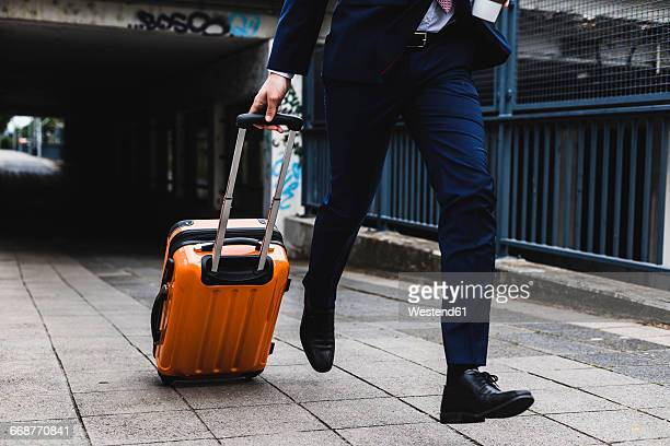 Businessman on business trip running with wheeled luggage