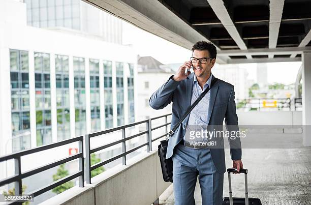 Businessman on business trip telephoning with smartphone