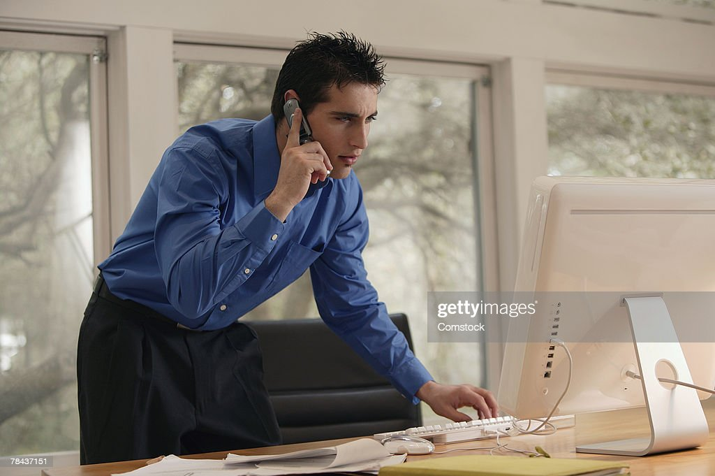 Businessman on cell phone and using desktop computer : Stockfoto