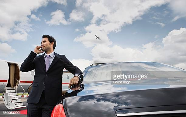 businessman on cell phone at airport - millionnaire stock pictures, royalty-free photos & images