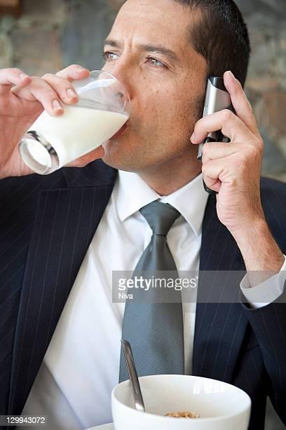 Empresário no telemóvel ao pequeno-almoço
